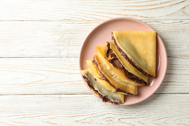 Plate of crepes with chocolate paste on white wooden surface