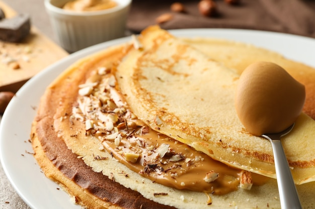 Plate of crepes with peanut butter and nuts, close up