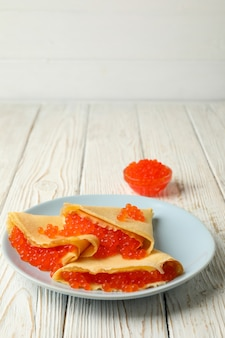Plate of crepes with red caviar on white wooden surface