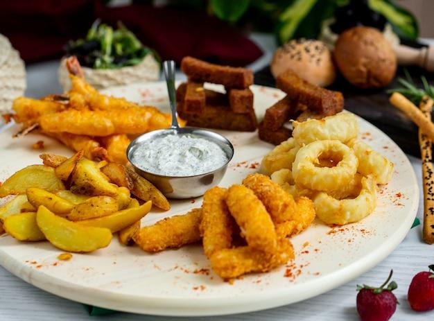 Piatto di calamari fritti croccanti, gamberi, crocchette di pomodoro e pollo e salsa