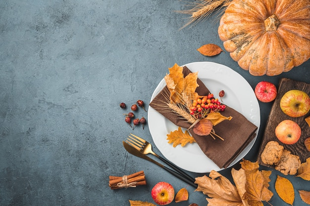 A plate cutlery autumn leaves apples and a pumpkin on a dark grayblue background