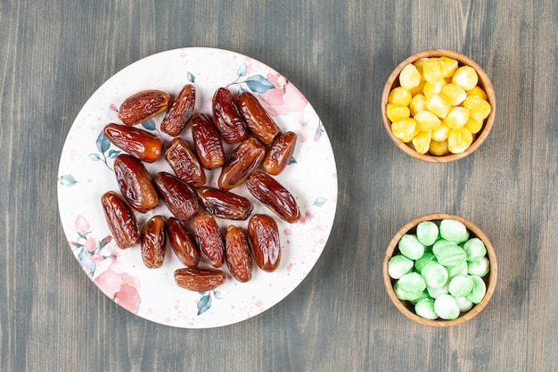 Plate of dates and colorful candies on wooden surface