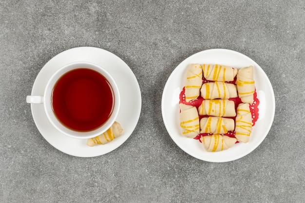 Piatto di deliziosi biscotti e tazza di tè sulla superficie in marmo