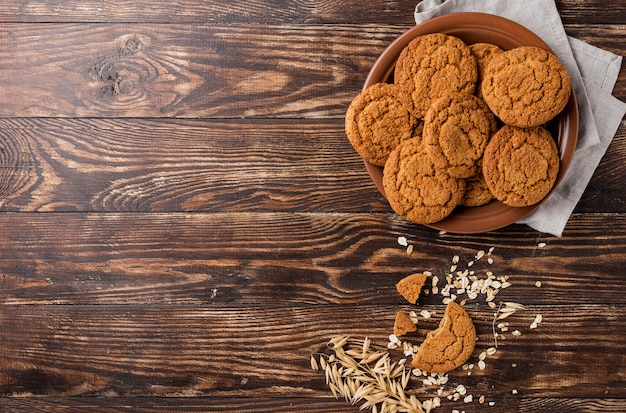 Plate of delicious cookies and wooden copy space background