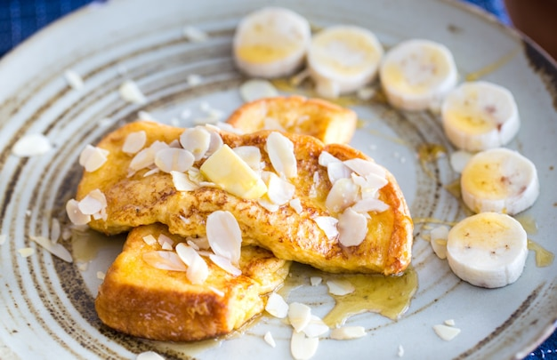 Plate of delicious french toast with bananas and maple syrup on top.