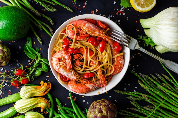 A plate of delicious italian pasta with tiger prawns or shrimps and fresh vegetables on black background