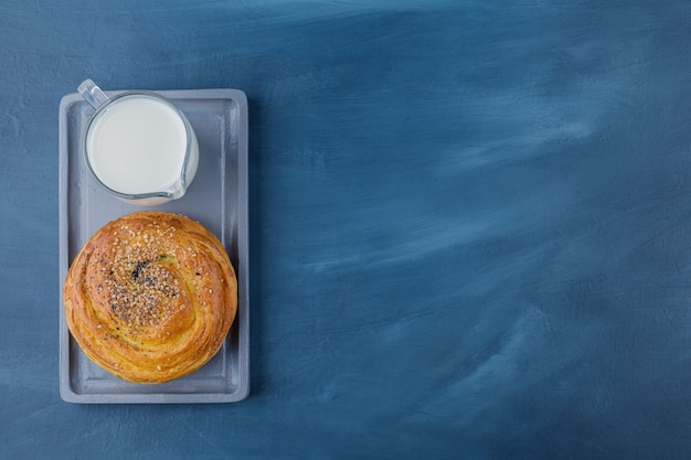Plate of delicious pastry with black seeds and glass of milk on blue surface.