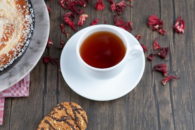 Un piatto di deliziosa torta con una tazza di tè nero posto su un tavolo di legno.