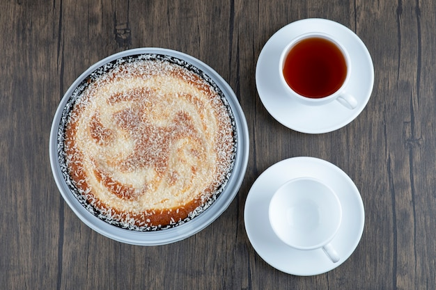 A plate of delicious pie with a cup of black tea placed on a wooden table .