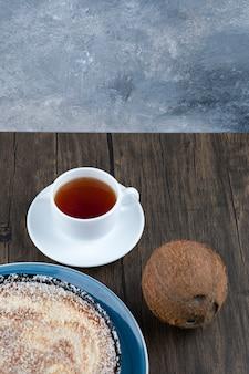 Un piatto di deliziosa torta con cocco intero fresco posto su un tavolo di legno.