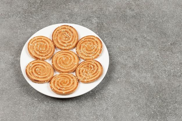 Piatto di deliziosi biscotti rotondi sulla superficie in marmo