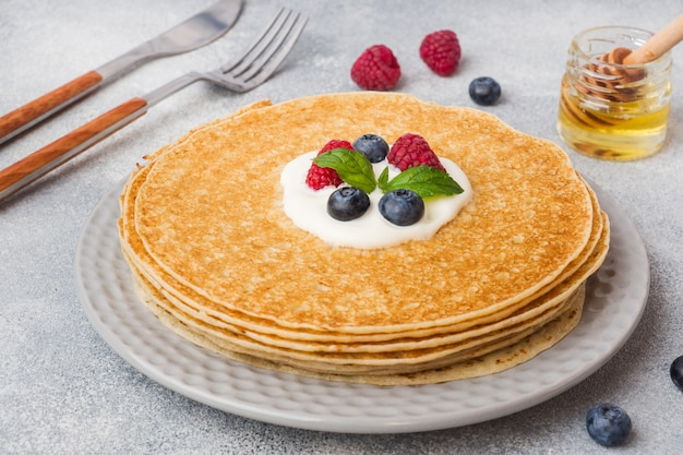 Plate of delicious thin pancakes with berries on grey table