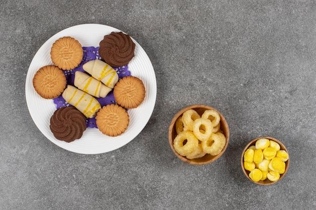 Piatto di dolci e caramelle su marmo.