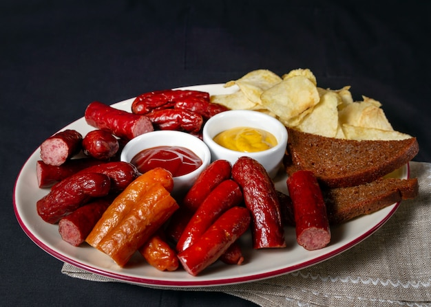 Plate of different beer snacks with sauces on dark