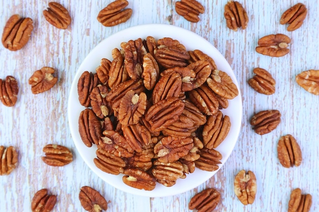 Plate of dried pecan nuts with some kernels scattered on wooden background