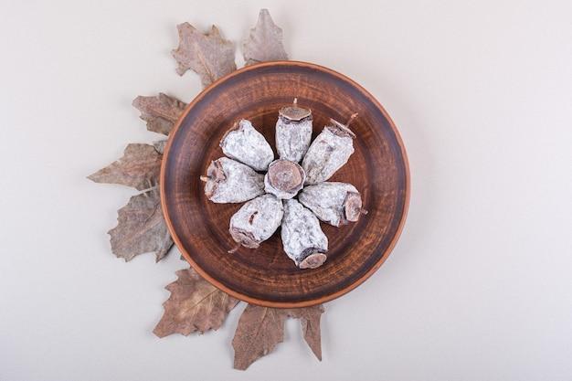 Piatto di cachi secchi e foglie secche su sfondo bianco. foto di alta qualità