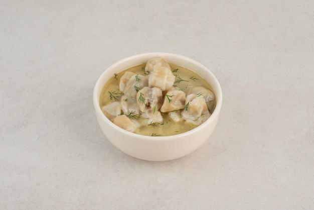 Piatto di gnocchi con verdure su sfondo bianco.