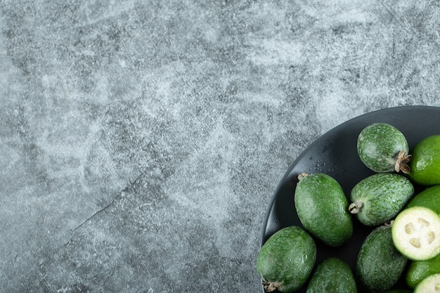 Plate of feijoa fruits on marble.
