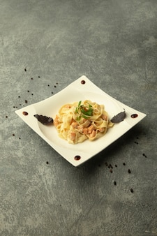 A plate of fettuccini with chicken in plain grey background