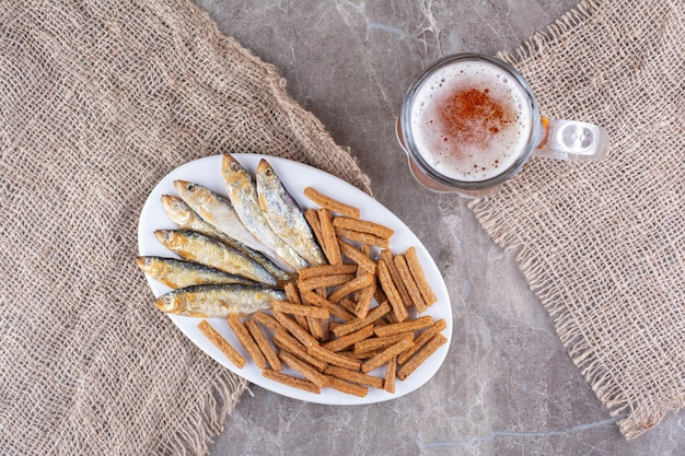 Plate of fish and crackers with beer on marble surface