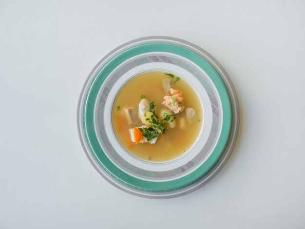 A plate of fish soup on a white table.