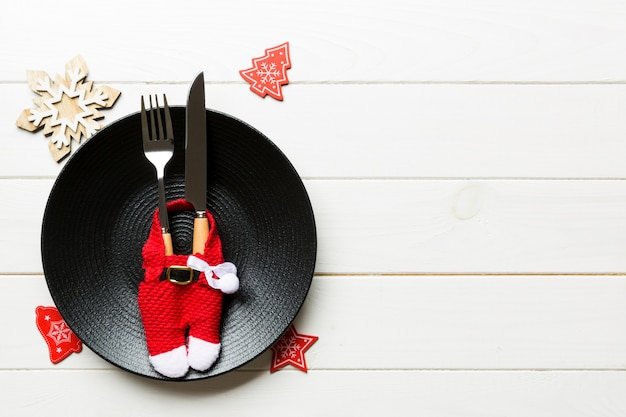 Plate and flatware decorated with santa clothes on wooden surface
