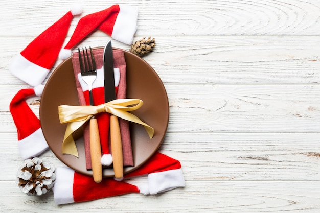 Plate and flatware decorated with santa hat on wooden surface