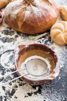 Piatto di farina e setaccio con panetteria sul tavolo