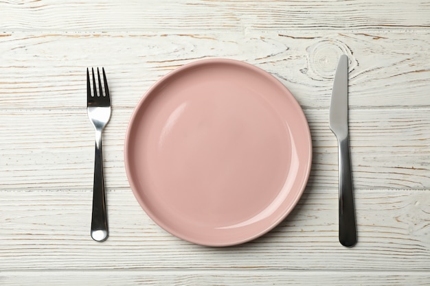 Plate, fork and knife on wooden background, top view