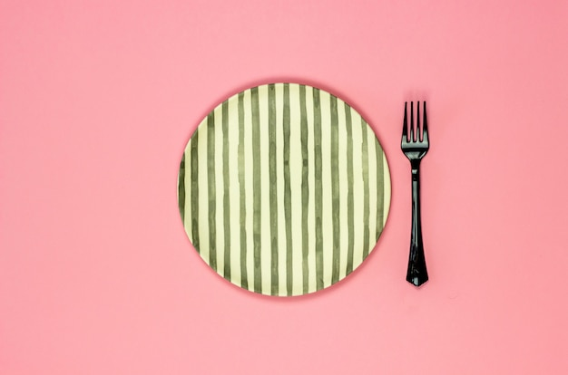 A plate and fork on a pink background. minimalism.