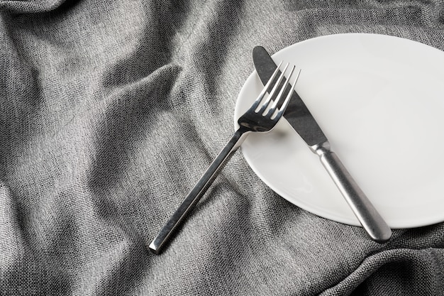 Plate fork spoon on fabric clothes background clear and without depth of field