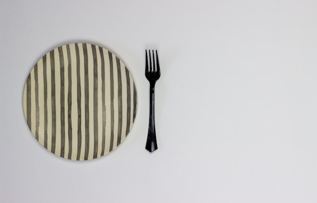 A plate and fork on a white background. minimalism.