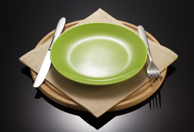 Plate and fork with knife at napkin cloth on black background
