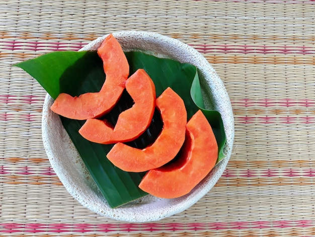 A plate of four pieces papaya on the banana leaf, fresh, sweet and good for health