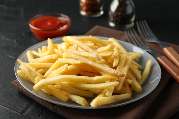 Plate of french fries, napkin, red sauce, forks on black. closeup