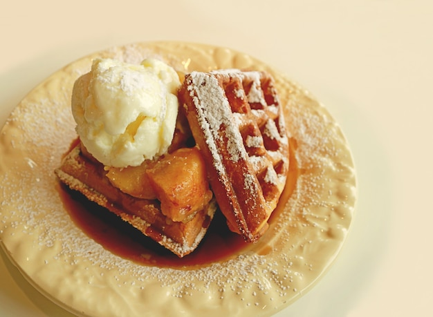Plate of fresh baked homemade cinnamon apple waffles topped with vanilla ice cream