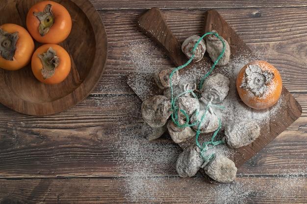 Piatto di fuyu fresco e frutta secca di cachi su tavola di legno
