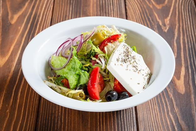Plate of fresh greek salad on wooden table