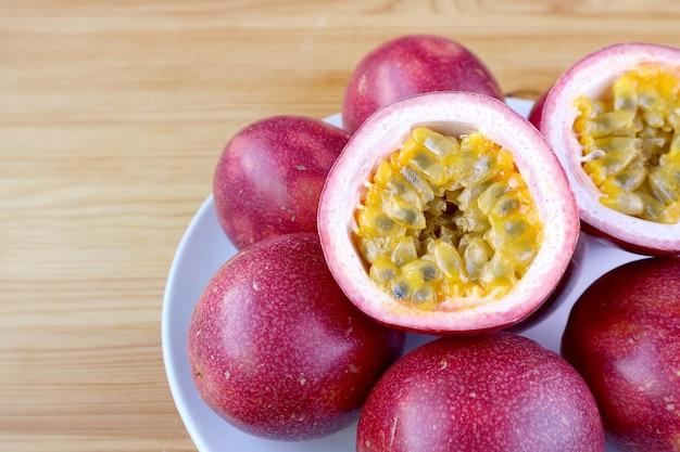 Plate of fresh ripe passion fruit with both cut on half and whole fruits