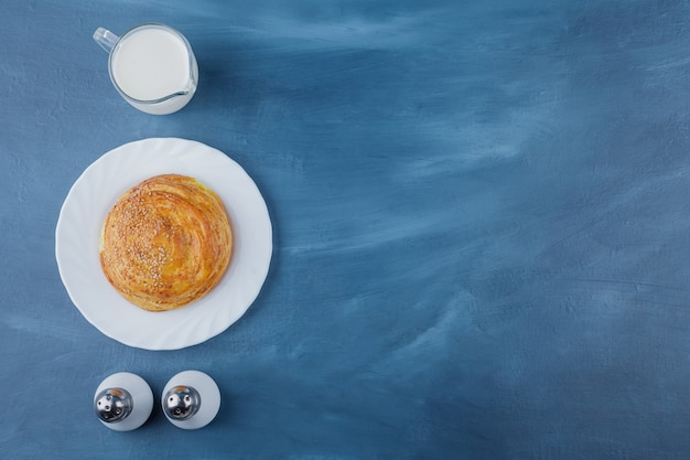 Plate of fresh round pastry with fresh milk on blue surface.