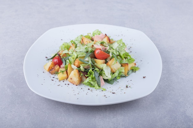 Piatto di insalata fresca con salsicce su fondo di pietra.