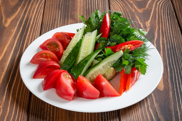 Plate of fresh vegetables and greens on wooden table