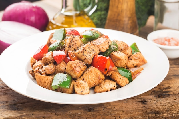Plate of fried chicken breast with colored pepper