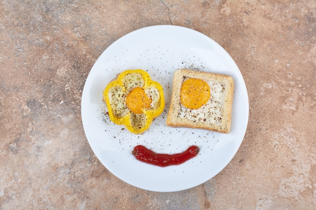 Plate of fried eggs with toast and spices on marble surface