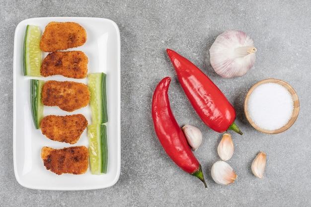 Piatto di pepite fritte e verdure fresche sulla superficie in marmo