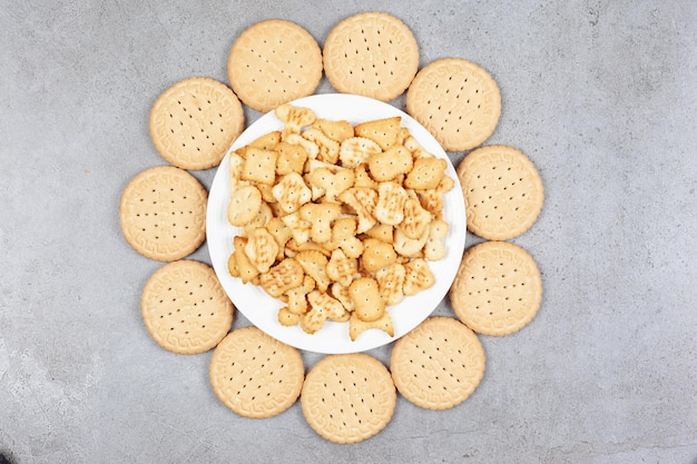 Plate full of cookie chips surrounded by biscuits on marble background. high quality photo