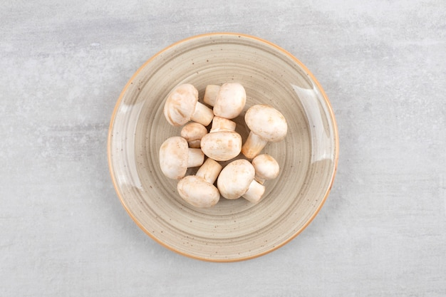A plate full of fresh champignon mushrooms placed on a stone surface.