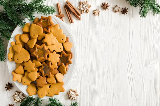 Plate full of freshly baked christmas gingerbread ready to decorate with icing on white wooden background. copy space