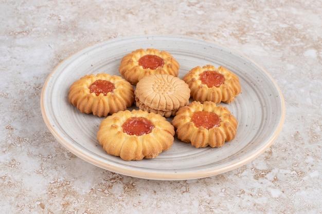 Un piatto pieno di biscotti di gelatina a forma di fiore su una superficie di pietra.