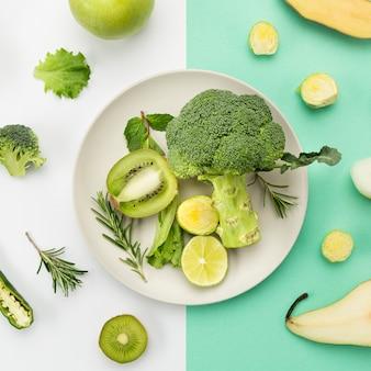 Тарелка, полная зеленых овощей и фруктов
